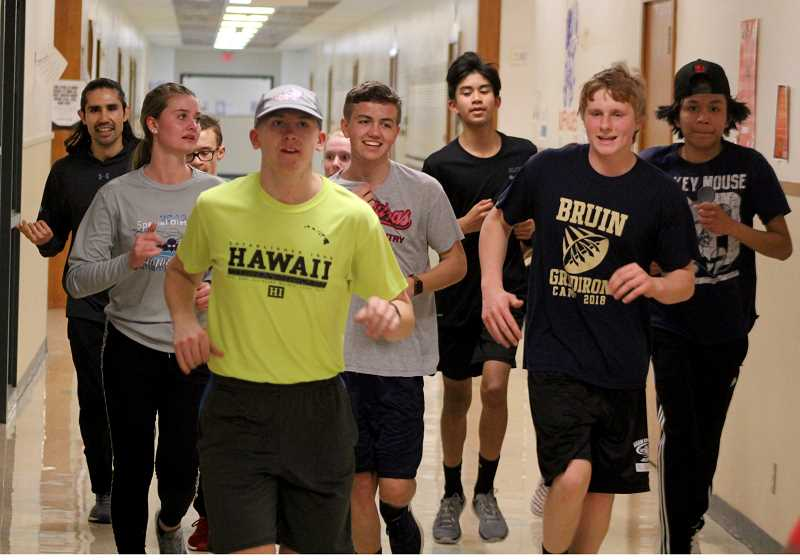 STEELE HAUGEN - Justin Plant (at left, yellow shirt) and Bryce Simmons, second from right, lead the way for the long distance Madras track and field runners. They ran through the halls of the school.