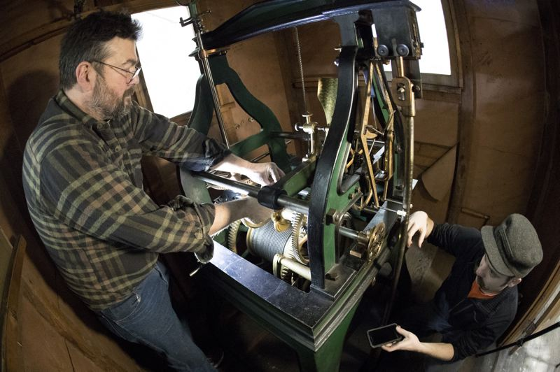 PORTLAND TRIBUNE: JAIME VALDEZ - John Pohlpeter (right) moves the hour hands of the four Union Station clocks ahead one hour for daylight saving time inside the clock tower on the evening of March 9. The mechanism is almost 125 years old. He is assisted by Kyle Nassman, who is checking the final setting with the digital clock on his iPhone.