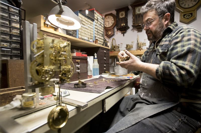PORTLAND TRIBUNE: JAIME VALDEZ - John Pohlpeter in his Father Time Clocks repair shop working on a small clock (left), which works much the same as the one at Union Station.