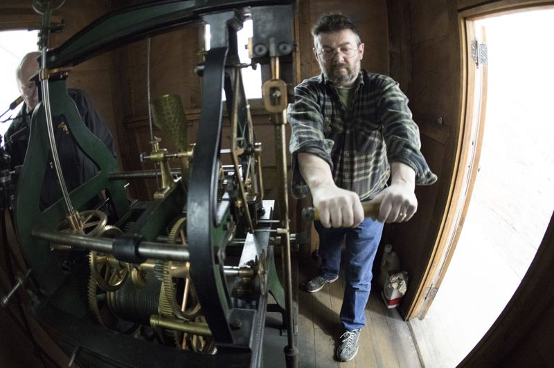 PORTLAND TRIBUNE: JAIME VALDEZ - John Pohlpeter winds the clock at Union Station after the hour hand is moved ahead for Daylight Saving Time. The 1896 Seth Thomas Clock Tower mechanism is on the left. A 500-pound weight must be hand-lifted every week to keep it running.