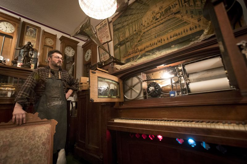PORTLAND TRIBUNE: JAIME VALDEZ - John Pohlpeter stands beside one of the many working player pianos and other musical relics he has restored and owned at his work shop.