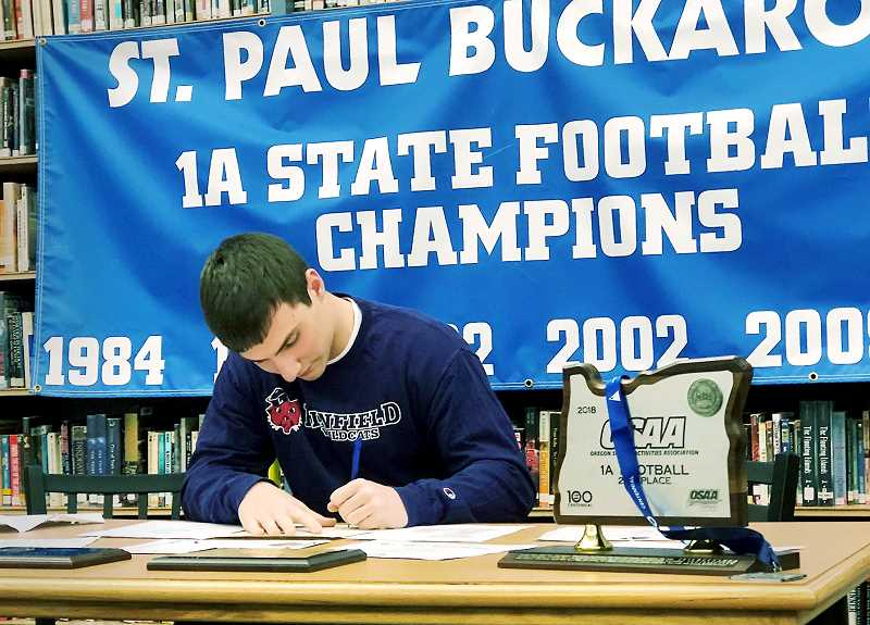 PHIL HAWKINS -- WOODBURN INDEPENDENT - Standout runningback/linebacker Justin Herberger signs his National Letter of Intent Thursday during a ceremony at SPHS.