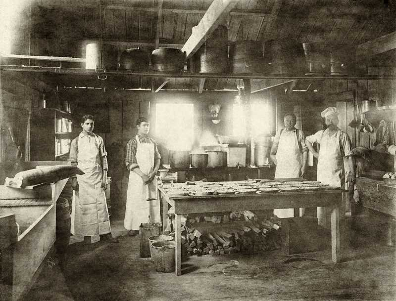 PHOTO AND RESEARCH BY JOHN KLATT OF OLD OREGON PHOTOS, WWW.OLDOREGONPHOTOS.COM - A logging camp cook shack — circa 1898: Pies are on the table of an early cook shack in this rare indoor photo, taken using only natural light. While basic (note the wood stacked beneath the table), the kitchen was essential for preparing food for the hungry loggers who burned as much as 8,000 calories during their 10-hour workdays. It appears the two old hands on the right are hoping to train their replacements. This image is by early photographer John F. Ford, who worked along both sides of the lower Columbia River, as well as in Portland.