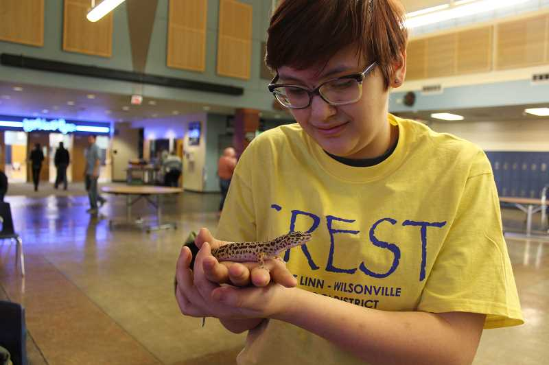 PMG PHOTO: HOLLY BARTHOLOMEW - Arts and Technology High School sophomore Grace Martin shows off CRESTs gecko, Sanders, to Science Symposium attendees.