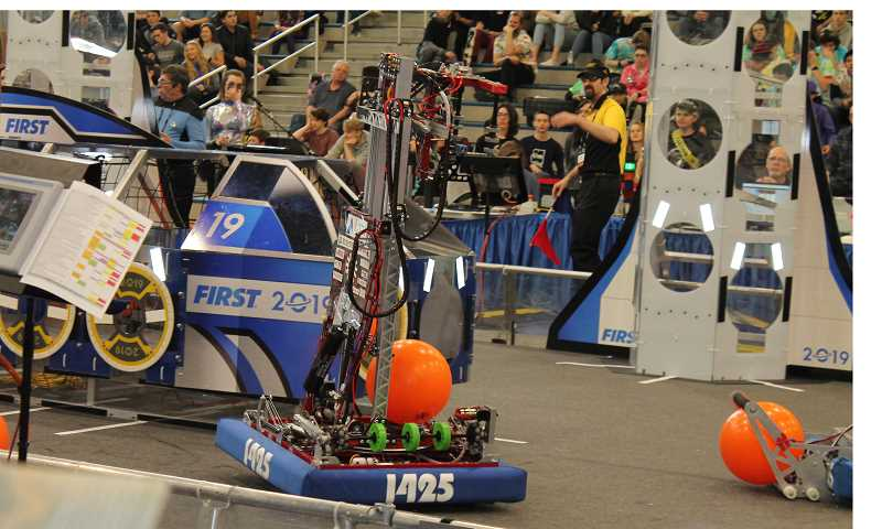 PMG PHOTO: HOLLY BARTHOLOMEW - Team 1425 Error Code Xeros robot controls a ball during a match at the district event at WHS.