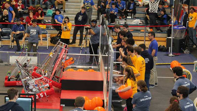 PMG PHOTO: HOLLY BARTHOLOMEW - 2B Determined members attempt to maneuver their robot onto a raised platform during a qualification match.
