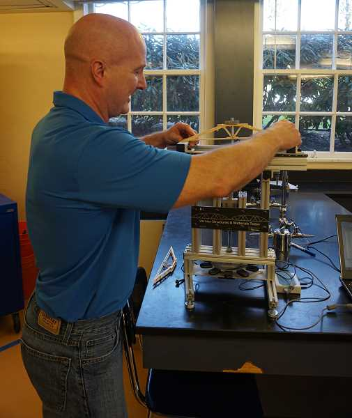 REVIEW PHOTO: CLAIRE HOLLEY - Riverdale physics and engineering teacher Mark Wechter shows how to use the Vernier structures and materials tester, invented by former LOHS teacher Tom Smith.