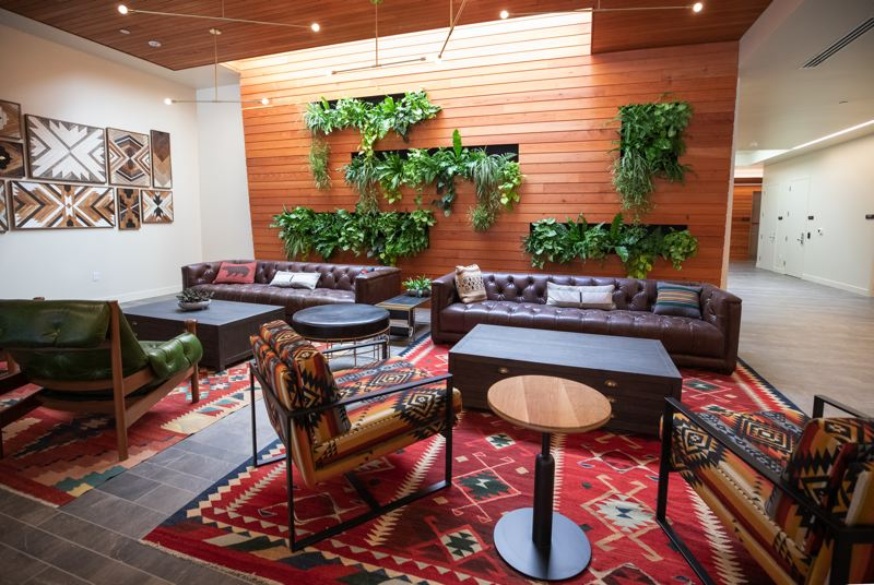 PAMPLIN MEDIA GROUP: JONATHAN HOUSE - The Carson's lobby is northwest adventure-themed. Behind the wood is a large Hub locker system for holding Amazon packages.