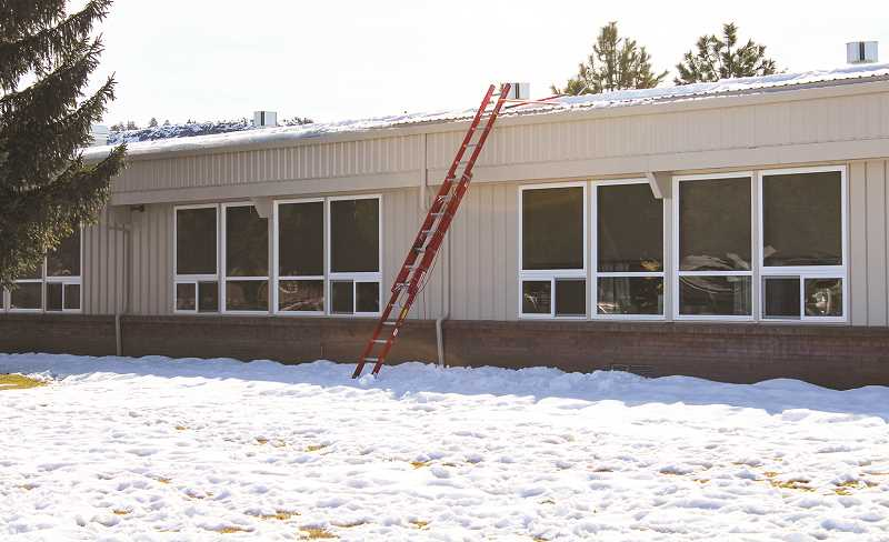 HOLLY SCHOLZ - The school district facilities crew removed snow from the edges of the building roofs to prevent damage.