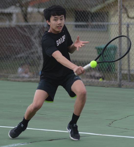 PMG PHOTO: DAVID BALL - Sandys Ethan Chang reaches out for a backhand return during his 6-4, 6-1 win in No. 1 singles.