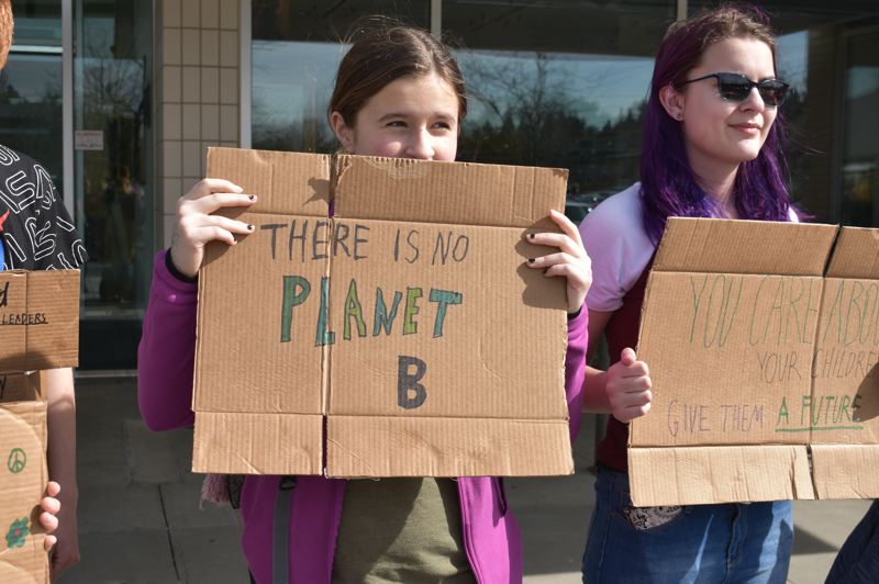 PMG PHOTO: TERESA CARSON - Students deployed used cardboard for their signs for minimal impact on the enviornment.