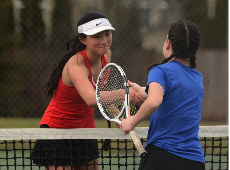 PMG PHOTO: DAVID BALL - Clackamas sophomore Elise Kang shakes hands with Barlow senior Gracy Maxey after her 6-1, 6-4 win in No. 1 singles Thursday.