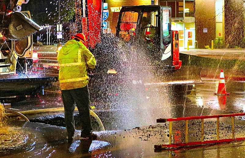 DAVID F. ASHTON - A Portland Water Bureau worker winces at being showered with cold Bull Run water while investigating the water main break on S.E. 82nd - which resembled a water feature more than a plumbing problem for several hours during the repair.