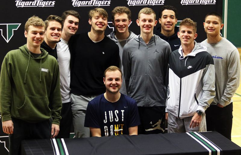 PMG PHOTO: DAN BROOD - Tigard High School senior Stevie Schlabach (seated), with his Tiger boys basketball teammates around him, signed to play college basketball at Northwest Christian University in Eugene.
