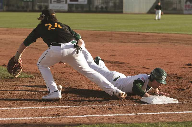 PMG PHOTO: PHIL HAWKINS - North Marion senior Nic Iliyn dives back to first on an attempted pick-off against the Sweet Home Huskies in last weeks home opener on March 13.