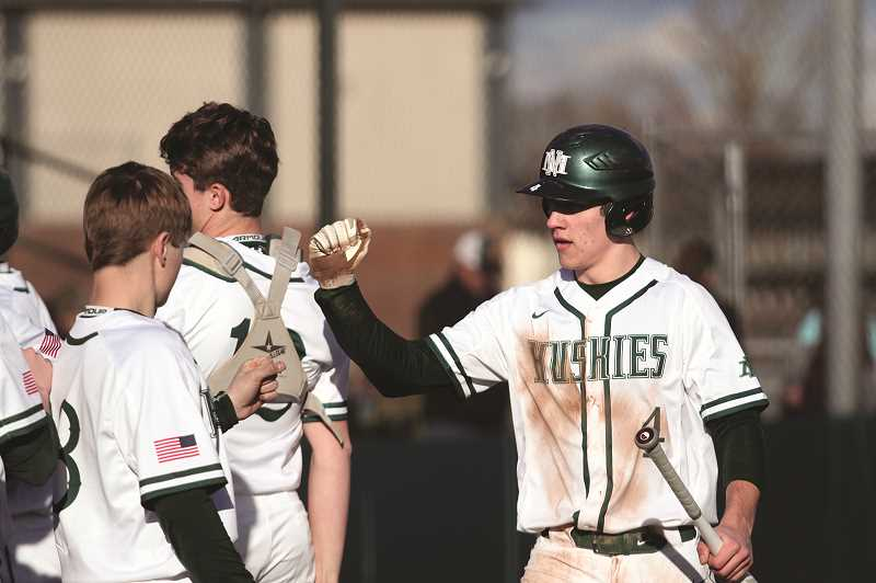 PMG PHOTO: PHIL HAWKINS - Iliyn bumps fists after scoring the Huskies opening run against Sweet Home. In four games last week, Iliyn was 7-for-12 with six runs , six RBIs, three walks, four stolen bases and a home run.