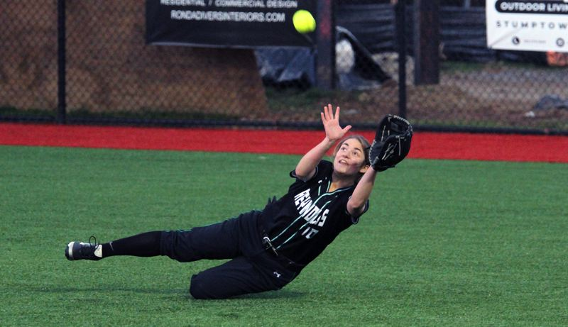 PMG PHOTO: MILES VANCE - Reynolds junior right fielder Kali Curtis gets ready to make a catch after her feet slipped out from under her in the fourth inning of the Raiders' 1-0 win at Lakeridge High School on Monday.