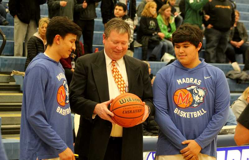 STEELE HAUGEN - Seniors Byron Patt (left) and Kahne Herkshan (right) give a basketball signed by this year's varsity basketball team to coach Evan Brown on his last game coaching the White Buffalos.