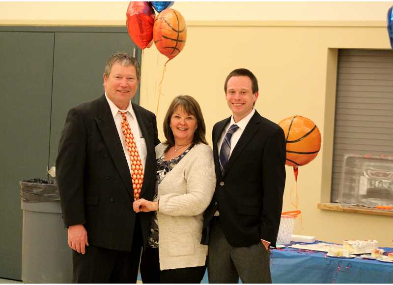 STEELE HAUGEN - Left to right, Evan, Amy and Nick Brown take a picture together during a reception for coach Evan Brown, celebrating his 18 years coaching Madras. Nick has followed in his father's footsteps and is the freshman boys basketball coach.