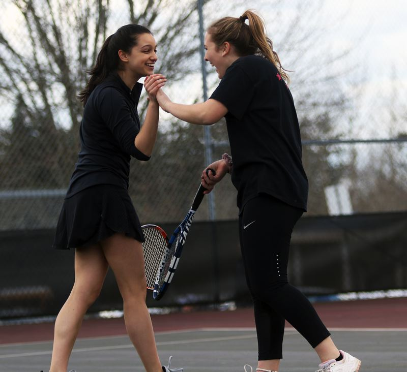 PMG PHOTO: DAN BROOD - Tualatin juniors Sophie Bennett (left) and Darci Chamberlin celebrate a point during the No. 1 doubles match when the Wolves hosted rival Tigard last week.