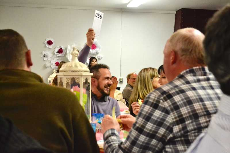 PMG FILE PHOTO - An attendee at last year's Estacada Chamber of Commerce Spring Gala bids during the events auction.