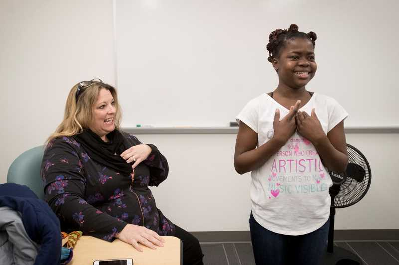 PMG PHOTO: JAIME VALDEZ - Kristi Park, a refugee coordinator with JustServe, watches as Venelle Imbi, a student at Meridian Creek Middle School, reacts after being told that she would be featured in the paper.