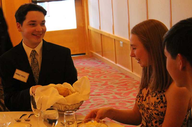 REVIEW PHOTOS: COREY BUCHANAN - Mitchell Weiss passed bread to Matigan Williams at the etiquette dinner Sunday, March 10, at Tualatin Country Club.
