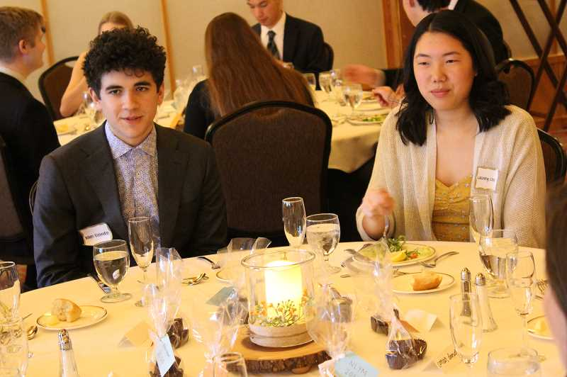 Noah Slobodin and Lainey Chi listen intently during a table conversation.