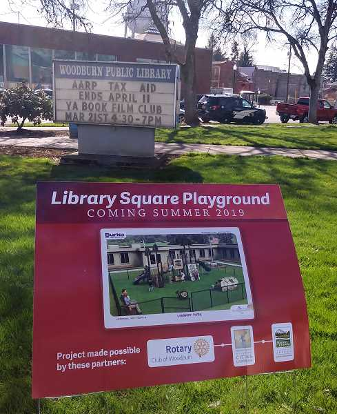 PMG PHOTO: JUSTIN MUCH - Sign touting the coming of Library Square Playground at First and Garfield streets underscores contributions for Rotary Club of Woodburn, Healthy Eating Active Living Cities Campaign, and  Marion County Health and Human Services.