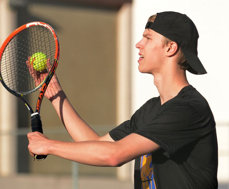 PMG PHOTO: DAVID BALL - Barlows Trevor Jones prepares to hit a serve during his three-set win at No. 3 singles.