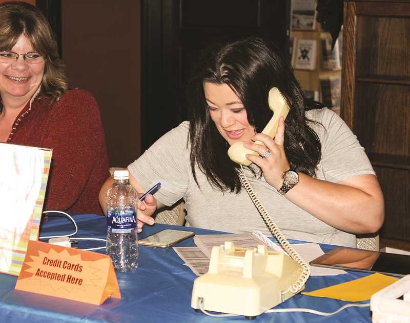 CENTRAL OREGONIAN FILE PHOTOS  - Rotarian Natalie Spry answers the phone during the event to take a silent auction bid.