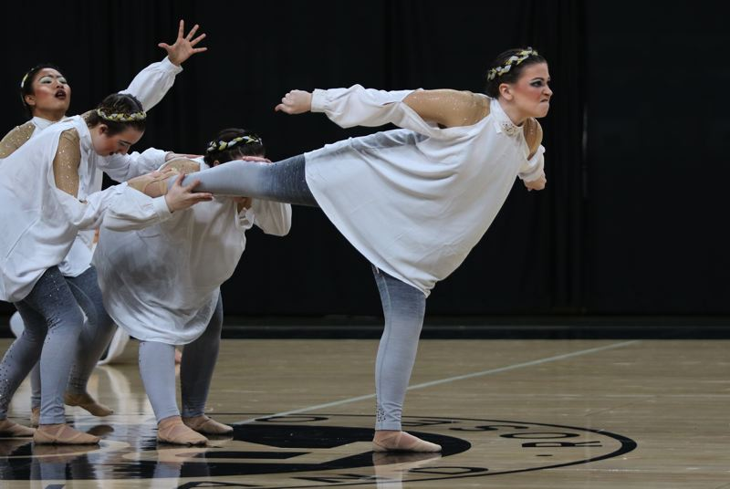 PMG PHOTO: JIM BESEDA - Archangels Cassidy Didier, CJ Vaughn and Baimon Boonyanon pull on fallen angel Hannah Darco in an effort to save her soul during the Scappoose Vision Dance Team performance of Fallen in the Class 5A championships.