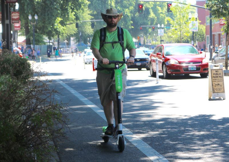 PMG PHOTO: ZANE SPARLING - An electric scooter rider zips through downtown Portland in summer 2018.