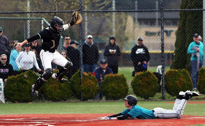 PMG PHOTO: DAN BROOD - Tigard senior catcher Caden Stinson (left) leaps high for the ball as Century junior Cooper Hewitt slides safely to home plate in the second inning of Saturday's game.
