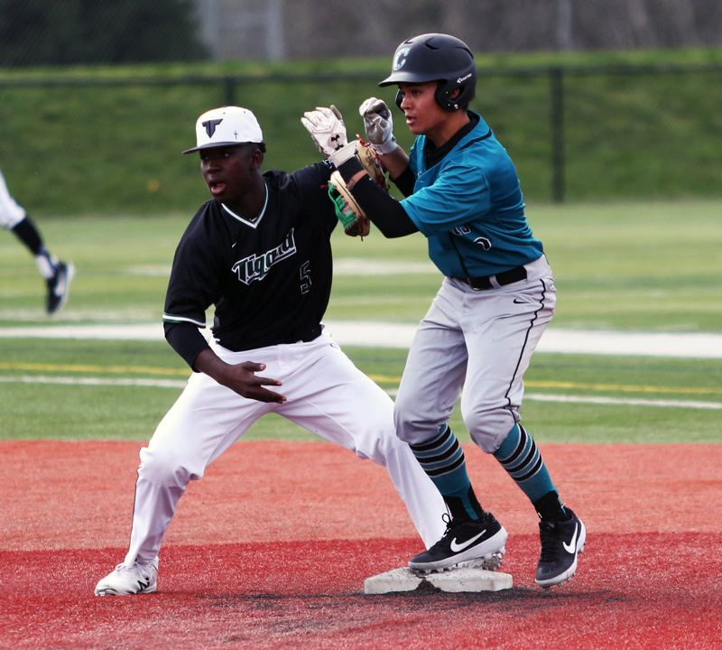 PMG PHOTO: DAN BROOD - Century senior Gene Quitagua (right), with Tigard sophomore shortstop Josh Schleichardt to his right) is safe at second on a stolen base attempt during Saturday's game.