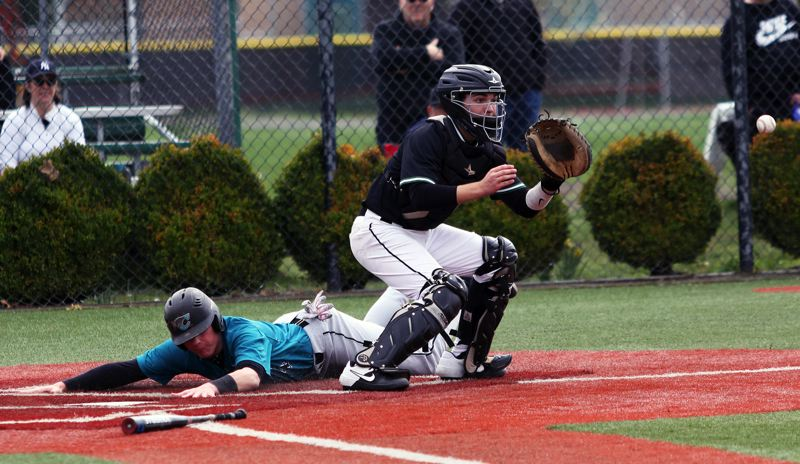PMG PHOTO: DAN BROOD - Century senior Justyn Herzog (left) slides safely to home plate, while Tigard senior catcher Caden Stinson awaits the ball, during Saturday's game.