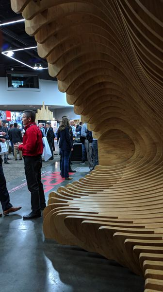 PAMPLIN MEDIA GROUP: JOSEPH GALLIVAN/COURTESY: FRERES LUMBER - At the International Mass Timber Conference in Portland last week, a staffer from Freres Lumber Company stands in front of a centerpiece designed by LEVER, to showcase how thin their wooden panels can be.