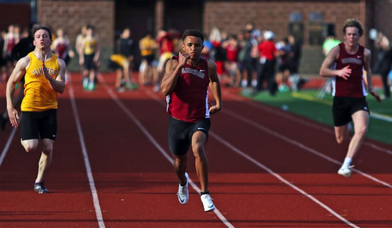 PMG PHOTO: DAN BROOD - Sherwood High School junior Caleb Hagan (center) is on his way to victory in the 100-meter dash during the Bowmen's win over Forest Grove.