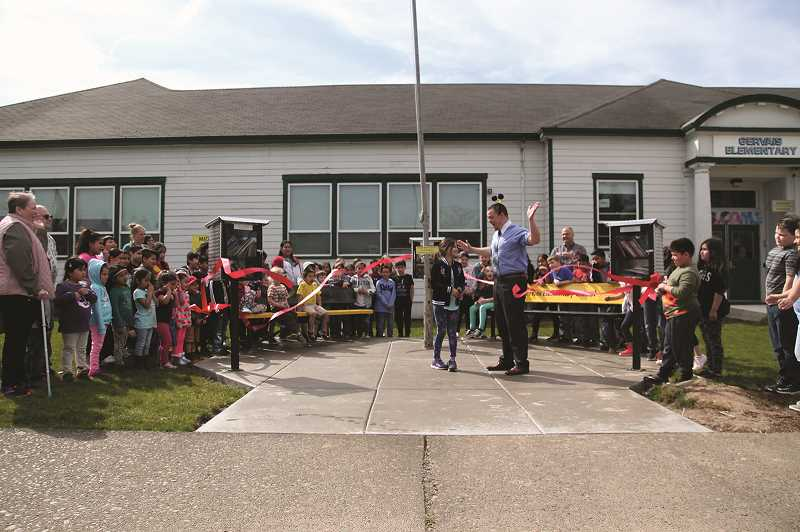 PMG PHOTO: PHIL HAWKINS - Students at Gervais Elementary School along with dignitaries from the community cut the ribbon on the school's Free Little Library reading area located in front of GES on March 19.
