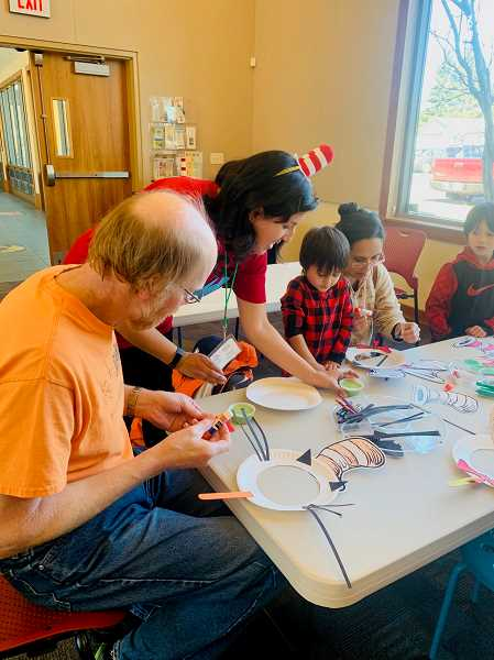 COURTESY PHOTO - Attendees of a recent bilingual story time at the Estacada Public Library work on a craft project.
