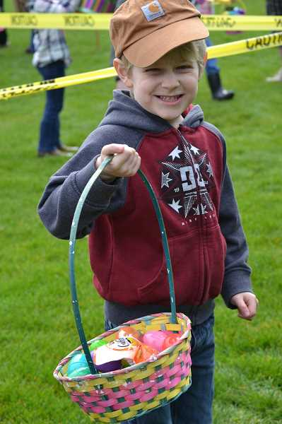 PMG FILE PHOTO - An attendee of last years Easter egg hunt shows off his findings. This years event is scheduled for 11 a.m. Saturday, April 20, at the Estacada Football Stadium.