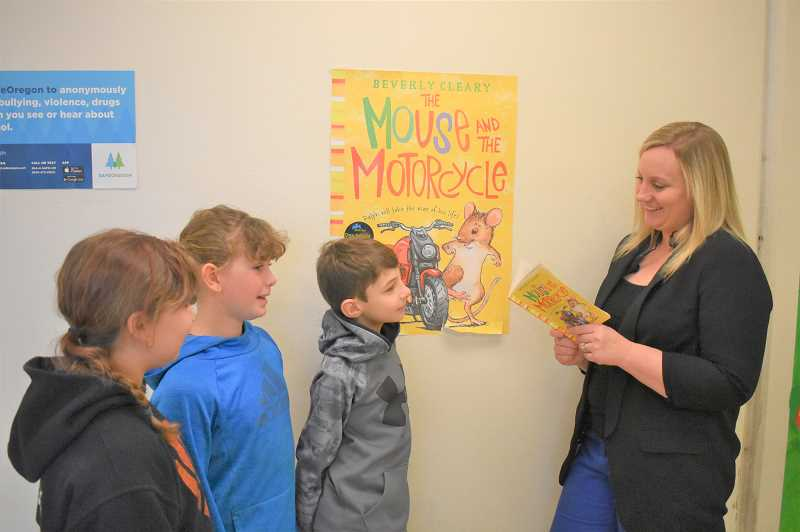 PMG PHOTO: EMILY LINDSTRAND - River Mill Elementary School Principal Jennifer Behrman reads 'The Mouse and the Motorcycle' to fourth graders Jacob Roan, Olivia Ferguson and Nickalila Faulk.