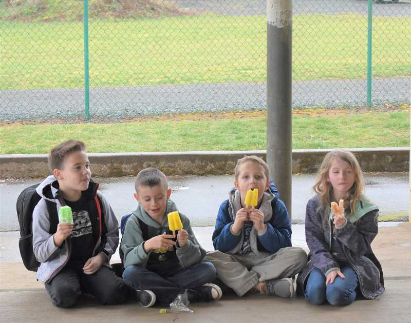 PMG PHOTO: EMILY LINDSTRAND - River Mill Elementary School students enjoy  mouse-sicles, or popsicles, in celebration of completing 'The Mouse and the Motorcycle' through the One School, One Book program.