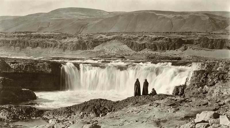 RESEARCH AND PHOTO BY JOHN KLATT OF OLD OREGON PHOTOS, OLDOREGONPHOTOS.COM - Celilo Falls on the Columbia - 1900: This view of three men looking over Celilo Falls is one of photographer Benjamin Giffords better-known photos, and rightly so. It combines excellent technical quality, good composition and a poignant story. Our version is restored from a sharp original boudoir card - a popular size of scenic photo about 4.5 x 7.5 inches. Note that the young man on the right is wearing western-style clothing. He may have been home visiting from one of the boarding schools of the time.
