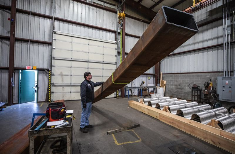TRIBUNE PHOTO: JONATHAN HOUSE - Albina Co.s Mike Frisbee inspects an enormous, metal stair stringer.  , Business Tribune - News Tualatin-based Albina Co. has provided bent steel for some of the country?¢'Ǩ'Ñ¢s biggest construction projects 