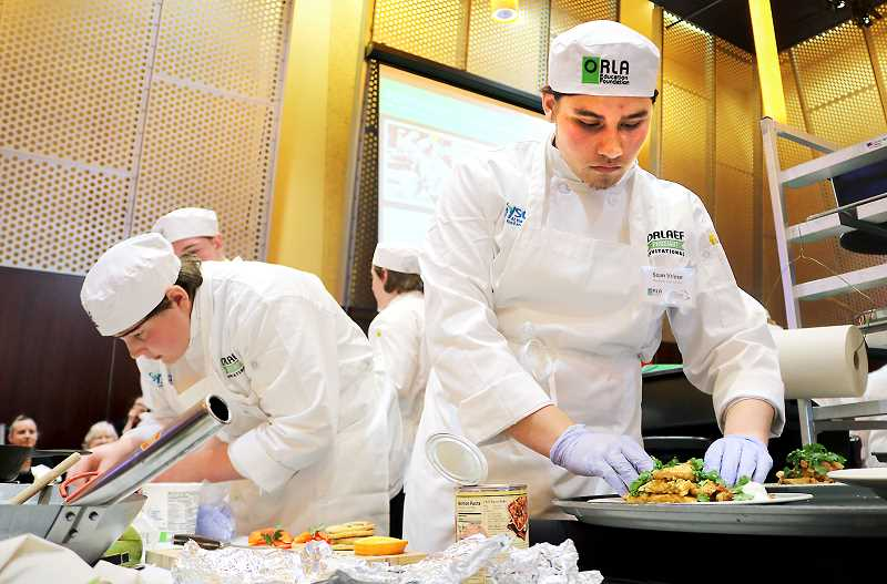 SUBMITTED PHOTO - Members of the Newberg High School culinary team prepare a meal during the ProStart Invitational Culinary Competition in early March at the Oregon Convention Center in Portland.
