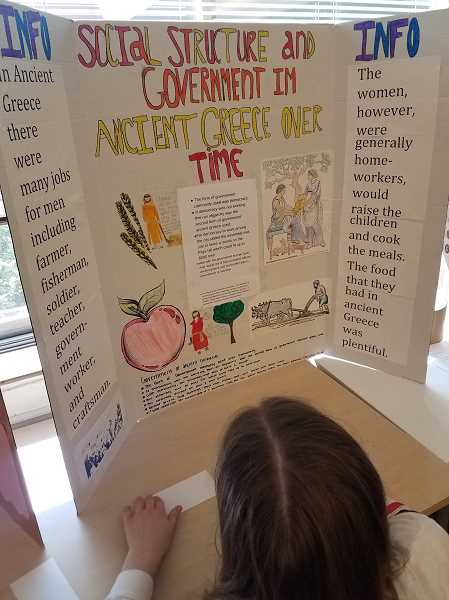COURTESY PHOTO - A sixth grader takes notes on her classmates project about the social structure and government of Ancient Greece.