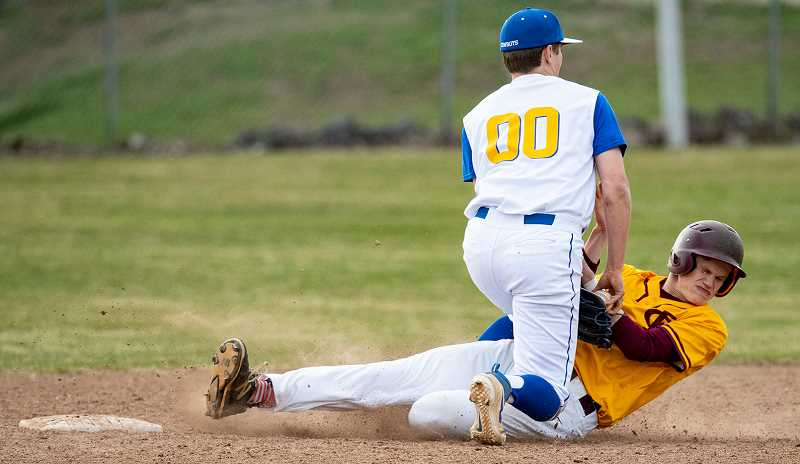 LON AUSTIN/CENTRAL OREGONIAN - Diego Smith tags out a Forest Grove runner who was attempting to steal second. Crook County catcher Brody Connell threw out two Forest Grove baserunners in the game as the Cowboys won 4-2.