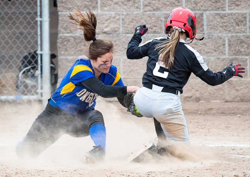 LON AUSTIN/CENTRAL OREGONIAN - Liz Barker tags out a Mountain View runner at third base during the Cowgirls' 23-2 victory over the Cougars Monday afternoon. Playing in the Redmond Invitational the Cowgirls went 3-1 during two days of play.