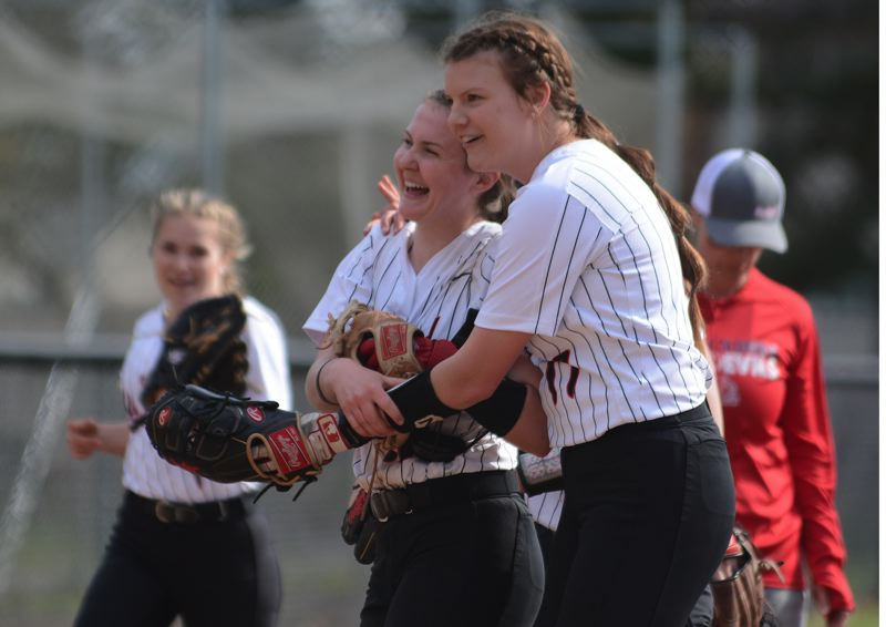 PMG PHOTO: DAVID BALL - Mt. Hood pitcher McKenzie Pierce embraces shortstop Bekah Roe after the Saints converted the final out in their 7-6 Game 1 win over Lower Columbia on Friday.